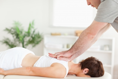 masseur: A masseur is massaging a female customers back in his surgery