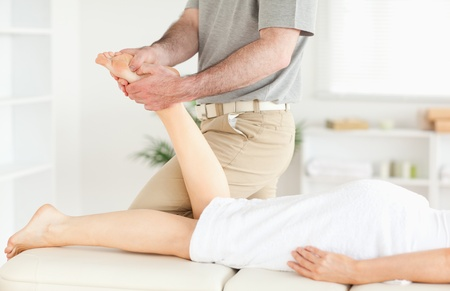A masseur is massaging a womans foot in his surgery photo