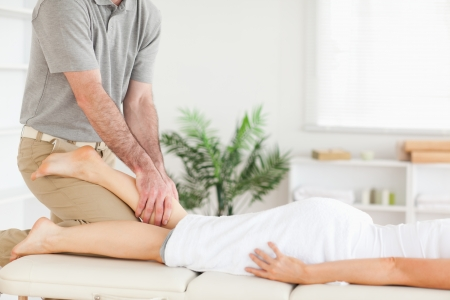 A masseur massages a womans leg  photo