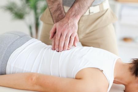 A masseur massages a customers back
