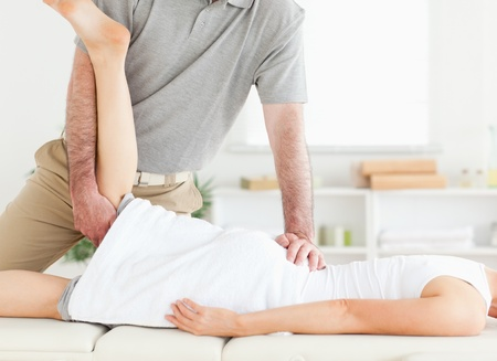 A chiropractor stretches a woman's leg in his surgery photo