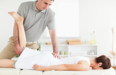 strength therapy: A chiropractor stretches a customers leg in his surgery Stock Photo