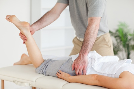 A chiropractor stretches a female customer's leg in his surgery photo