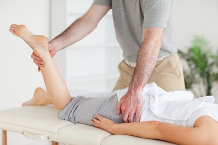 akupressur: Ein Chiropraktiker erstreckt sich eine Kundin das Bein in seiner Praxis