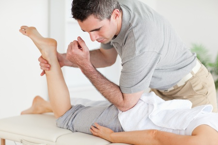 acupressure hands: A chiropractor stretches a womans leg in a surgery Stock Photo