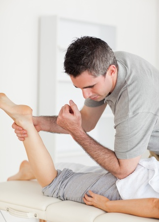 A chiropractor stretches a female customer's leg in a surgery photo