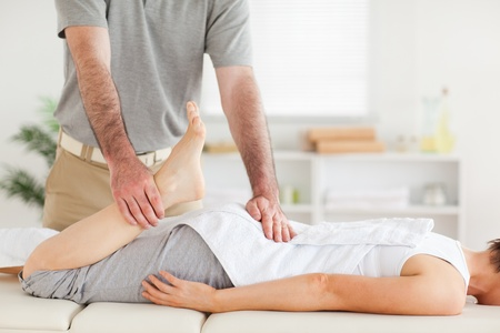 physical pressure: A chiropractor stretches womans leg in his surgery