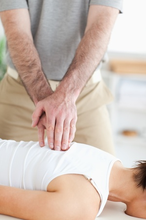 acupressure hands: A masseur massages a womans back in his surgery Stock Photo
