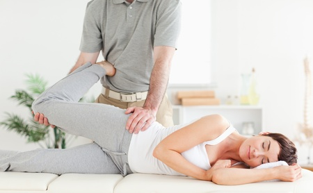 A woman's leg is stretched by a chiropractor photo