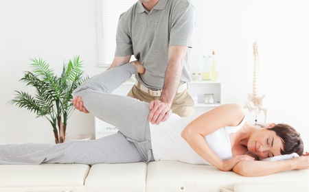A female customer's leg is stretched by a chiropractor in his surgery photo