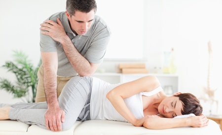 A masseur is massaging a womans hip  photo