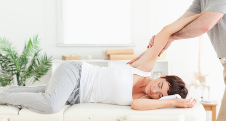 A chiropractor is stretching a womans arm photo
