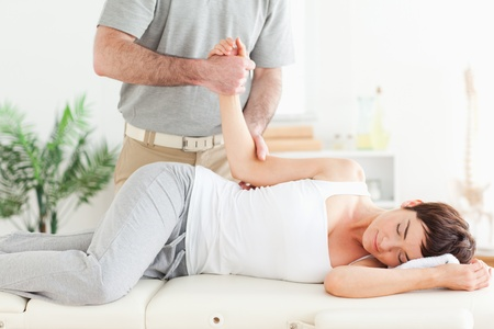 acupressure hands: A chiropractor stretches a womans arm in his surgery Stock Photo