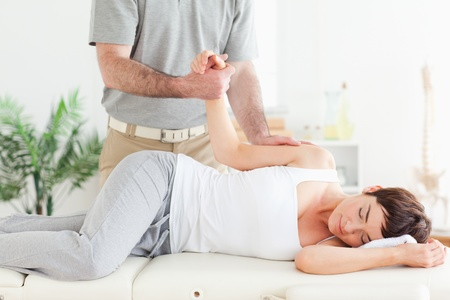 A chiropractor stretches a female customer's arm in his surgery photo