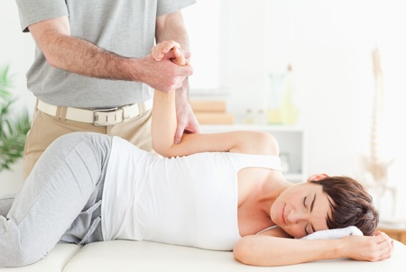 A chiropractor stretches a customers arm in his surgery photo