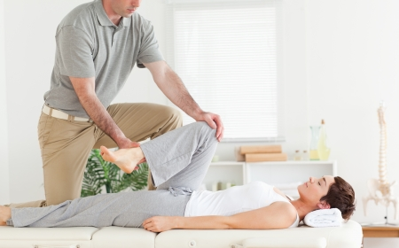 A chiropractor stretches womans arm in his surgery photo
