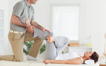 A chiropractor is stretching a woman's leg photo