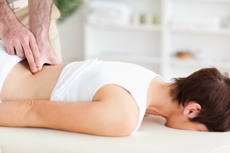 A chiropractor is massaging a woman photo