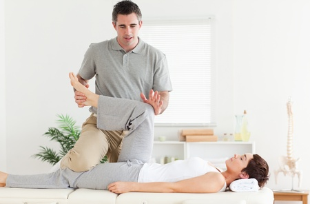 strength therapy: A chiropractor is stretching a womans leg
