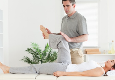 A chiropractor is stretching a customers leg photo