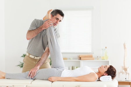 A chiropractor is exercising with a woman photo