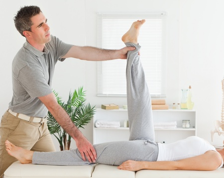 A chiropractor is exercising with a customer photo