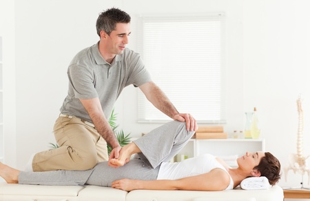 A chiropractor is stretching a female customer's leg photo