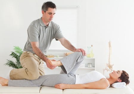 A chiropractor is stretching a young woman's leg photo