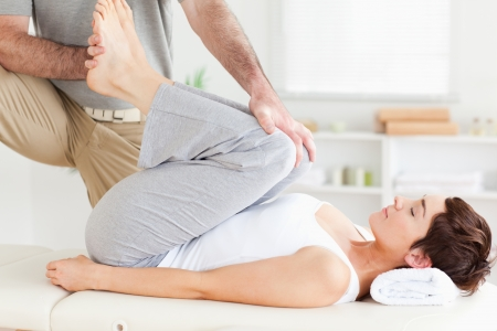 A chiropractor is stretching a woman's legs photo