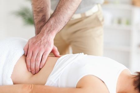 A masseur is massaging a woman photo