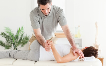 strength therapy: A masseur is stretching a womans arm