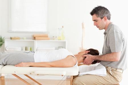 física: Un masajista es estirar la cabeza de una mujer
