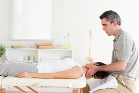A chiropractor is massaging a womans neck in his surgery photo