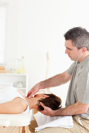 A chiropractor is massaging a female customers neck in his surgery photo