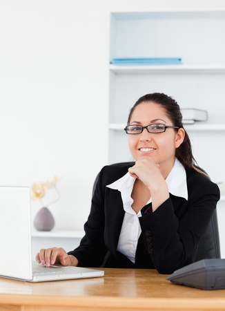A young businesswoman with glasses sitting at her workplace photo