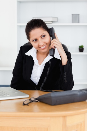 A smiling businesswoman is telephoning in her office photo