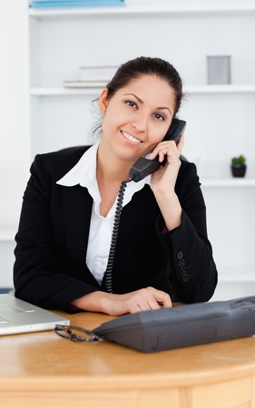A Smiling businesswoman on the telephone in her office photo