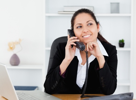 A beautiful smiling businesswoman on the telephone in her office photo
