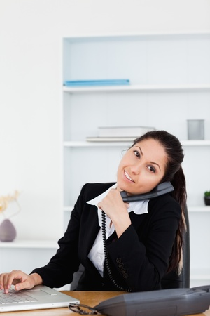 A happy businesswoman typing on keyboard whilst telephoning  photo