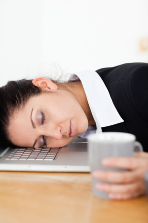 A businesswoman is sleeping with her head on laptop whilst holding a cup of coffee photo