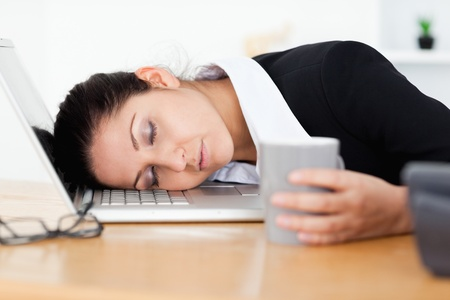 An exhausted businesswoman is sleeping with her head on laptop photo