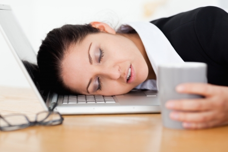 tired: An exhausted businesswoman is sleeping with her head on her keyboard Stock Photo