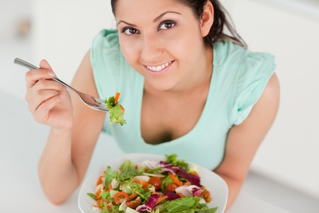 A cute young woman eating a salad  photo