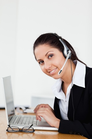A smiling young operator with a headset is helping someone via headset in her office photo