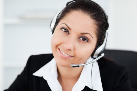 A cute smiling businesswoman with a headset in her office photo