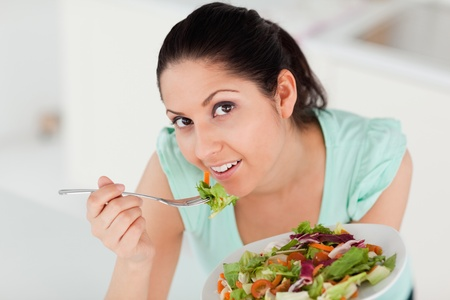 A beautiful woman is eating a salad photo