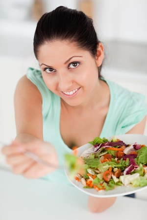 A cute young woman is offering salad in her kitchen photo