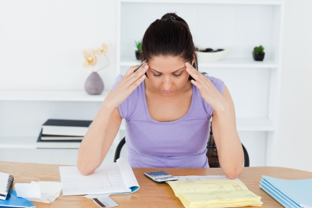 A stressed young woman is accounting photo