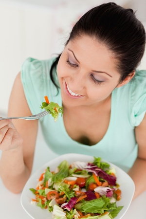 A smiling young female is eating salad photo