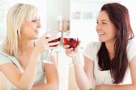 Joyful Frauen Toasten mit Wein in einer K�che
